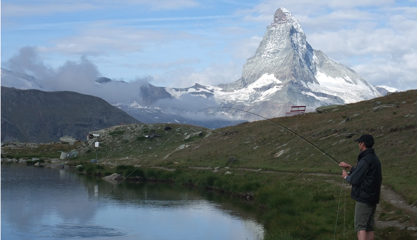 Fly Fishing in Switzerland, hooking up on a trout in front of the Matterhorn