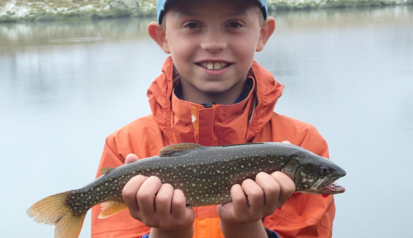 Fly Fishing in Switzerland, young man catches beautiful lake trout